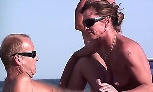 French nudist couple doing a hand- and blowjob in public on the beach