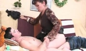 Caring mom massages a slim lad and later saddles his cock